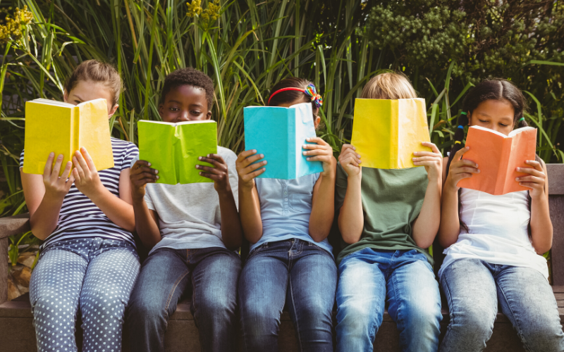 five children sitting reading brightly coloured books